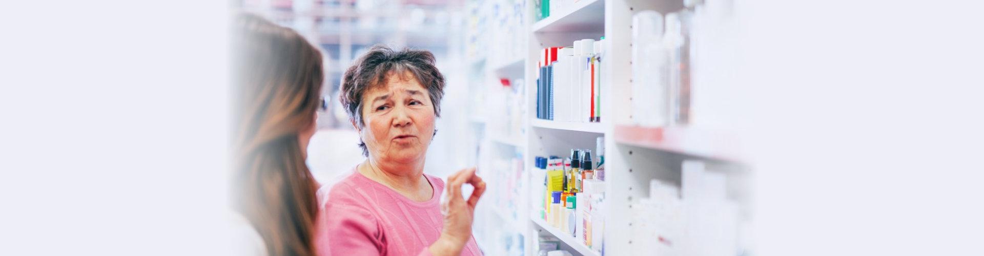 pharmacist discusses medication assortment with senior customer